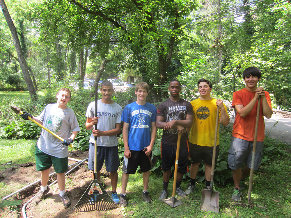 Ryan Dostillio (center in blue shirt) is one of two Boy Scouts who will complete his Eagle Scout project at the Rose Valley Heritage Garden and Veteran's Memorial. His portion includes rebuilding the stone retaining wall behind the gatehouse ruins and providing low voltage lighting on the fountain, the Mercer tile RV on the garage and the Will Price pillars at the end of Old Mill Lane. An Eagle Scout project is intended to show leadership skills, and Ryan did a fine job in leading his fellow scouts in completing his project despite the 100 degree weather. Special thanks to Dan Seifrit, of Seifrit Electrical Associates in Wallingford, PA for the donation of his time and materials to make this project possible.